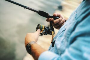 person holding black and yellow fishing reel